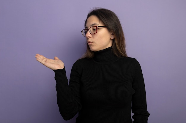 Giovane bella ragazza in un dolcevita nero e occhiali che presentano qualcosa con il braccio sulla sua mano