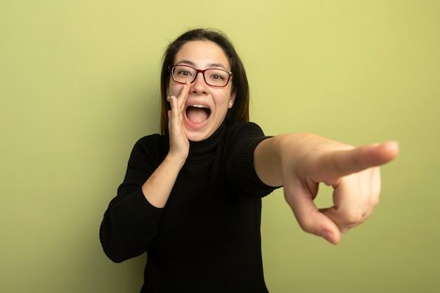 Giovane bella ragazza in un dolcevita nero e occhiali che grida con la mano vicino alla bocca che punta con il dito indice a qualcosa