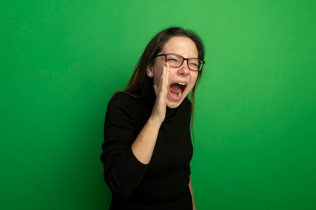 Young beautiful girl in a black turtleneck and glasses shouting with hand near mouth