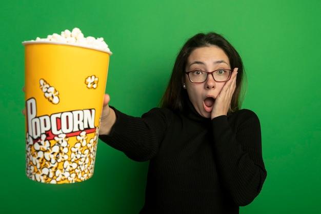 Giovane bella ragazza in un dolcevita nero e occhiali che mostrano secchio con popcorn stupito e sorpreso