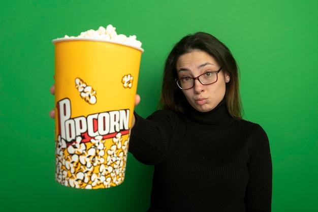 Giovane bella ragazza in un dolcevita nero e occhiali che mostrano secchio con popcorn confuso