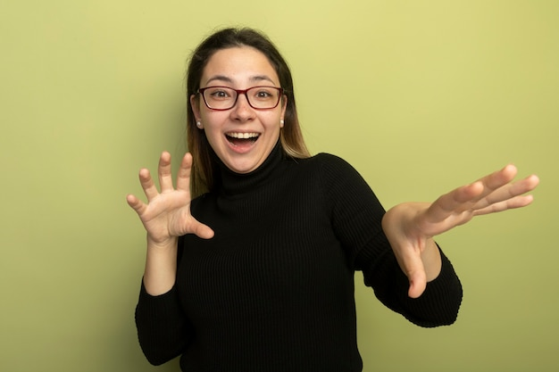Giovane bella ragazza in un dolcevita nero e occhiali sorridenti che tengono le mani confuse