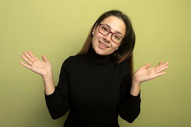 Giovane bella ragazza in un dolcevita nero e occhiali sorridenti allargando le braccia ai lati