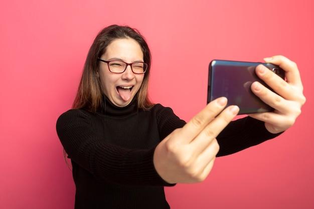 Giovane bella ragazza in un dolcevita nero e occhiali utilizza lo smartphone facendo selfie sorridente con la faccia felice che attacca fuori la lingua