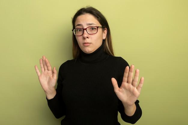 Giovane bella ragazza in un dolcevita nero e occhiali con espressione di paura che tiene le mani