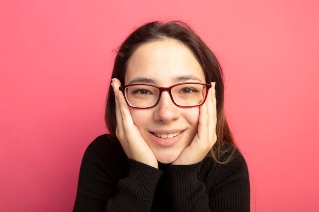 Giovane bella ragazza in un dolcevita nero e occhiali con le mani sul viso sorridendo allegramente