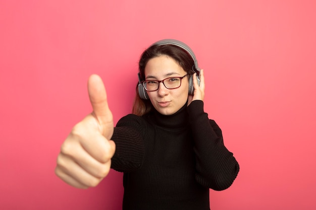 Young beautiful girl in a black turtleneck and glasses with headphones with smile on face showing thumbs up