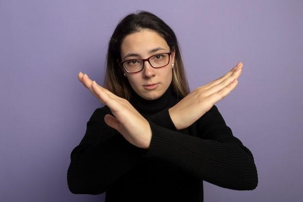 Giovane bella ragazza in un dolcevita nero e occhiali con faccia seria che fa gesto di stp attraversando le mani