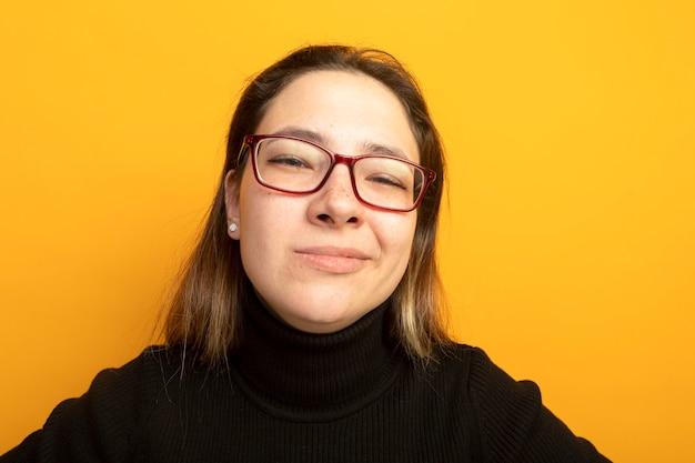Giovane bella ragazza in un dolcevita nero e occhiali con espressione scettica
