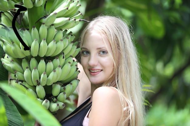 Молодая красивая девушка со светлыми волосами, стоя у бананового дерева