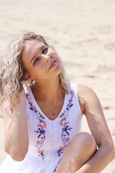 Young beautiful girl, blonde with hair developing from the wind against the sandy shore