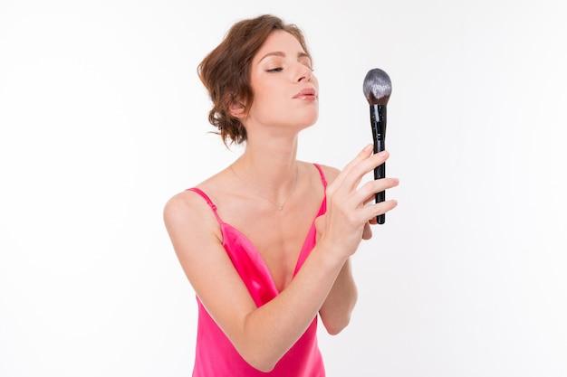 Молодая красивая девушка дует на макияж кисти с пудрой на белом фоне