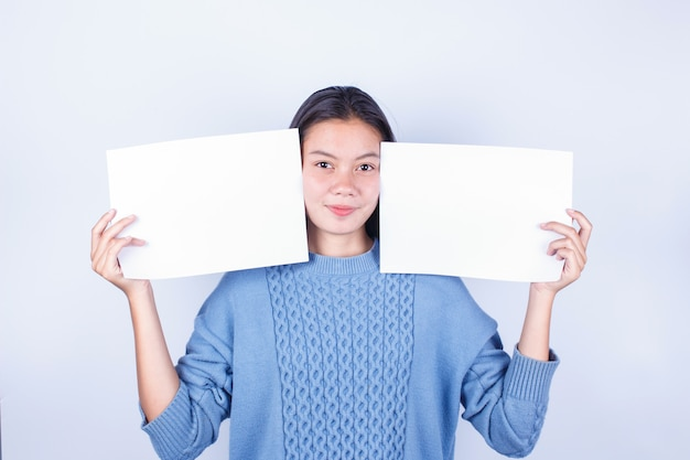Young beautiful girl in blue sweater holding empty white paper and space for text on gray background