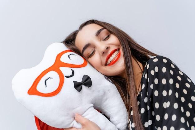 Молодая красивая девушка закрыла глаза и положила голову на мягкую игрушку в форме зуба.