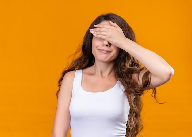 コピースペースと孤立したオレンジ色の壁に手で目を閉じる若い美しい少女