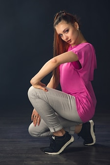 黒の背景にヒップホップを踊る若い美しい少女ダンサー