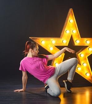 ランプの背景を持つ星にヒップホップを踊る若い美しい少女ダンサー