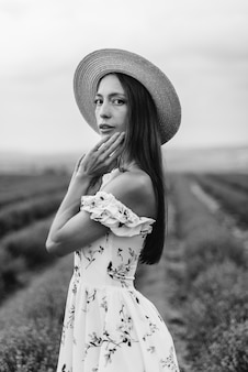 A young beautiful girl in a delicate dress and hat walks through a beautiful field of lavender and enjoys the aroma of flowers. vacation and beautiful nature. black and white.