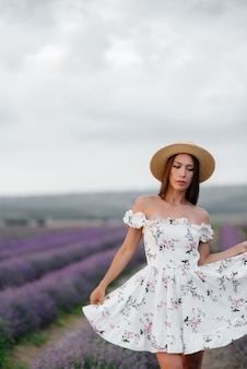 A young beautiful girl in a delicate dress and hat walks through a beautiful field of lavender and enjoys the aroma of flowers. vacation and beautiful nature.