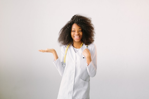 청진기를 가진 백색 외 투에서 젊은 아름 다운 여자 의사. 흰색 배경에