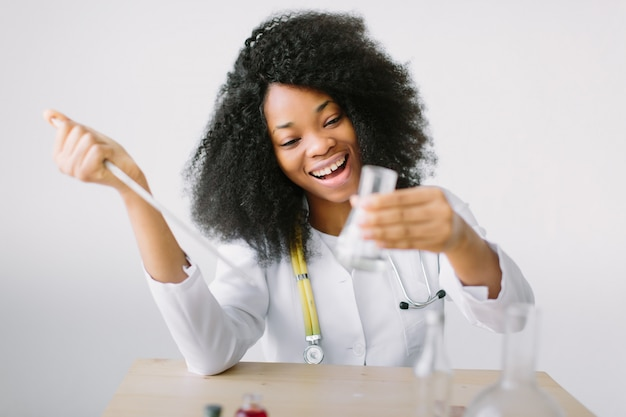 Young beautiful  girl doctor in a white coat with a stethoscope. sitting at a table and analyzing sample in laboratory.laboratory assistant analyzing a sample.