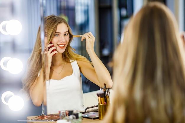 거울 앞에서 화장을 하고 휴대전화로 통화하는 젊은 아름다운 소녀.