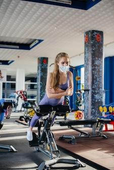 전염병 동안 마스크를 쓰고 체육관에서 운동을 하는 젊은 아름다운 소녀. 공공 장소에서의 사회적 거리두기.