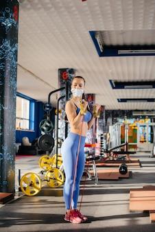パンデミック時にマスクを着用してジムでスポーツをしている若い美しい少女。公共の場所での社会的距離。