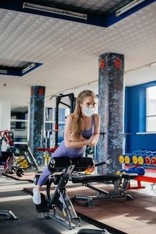 유행성 동안 마스크를 쓰고 체육관에서 스포츠를 하 고 젊은 아름 다운 소녀. 공공 장소에서의 사회적 거리두기.