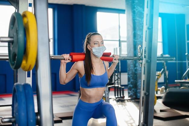 전염병 동안 마스크를 쓰고 체육관에서 스포츠를 하는 젊은 아름다운 소녀