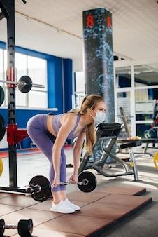 유행성 동안 마스크를 쓰고 체육관에서 스포츠를 하 고 젊은 아름 다운 소녀