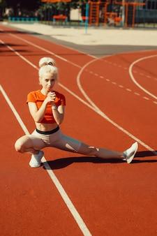 Молодая красивая девушка делает разминку перед спортивными упражнениями на школьном стадионе