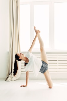 Young beautiful girl doing warm-up contemporary at home