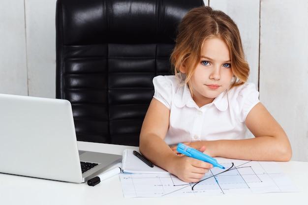 Giovane bello grafico del disegno della ragazza al posto di lavoro in ufficio.