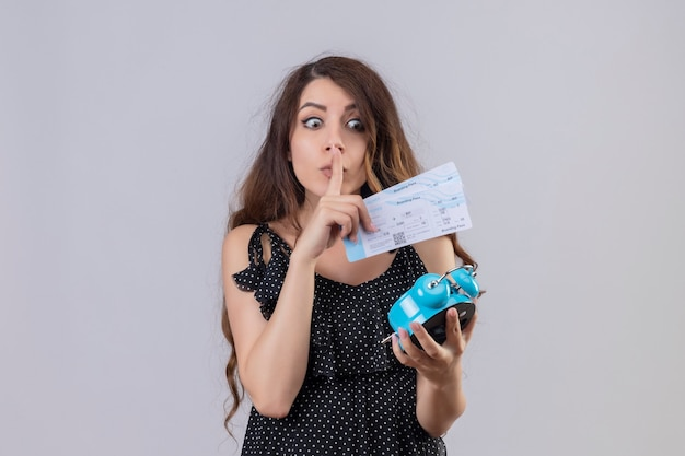 Young beautiful girl in dress in polka dot holding alarm clock and air tickets making silence gesture with finger on lips standing over white background