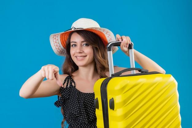 Giovane bella ragazza in abito a pois in cappello estivo che tiene la valigia che punta alla telecamera con un sorriso fiducioso sul viso in piedi su sfondo blu