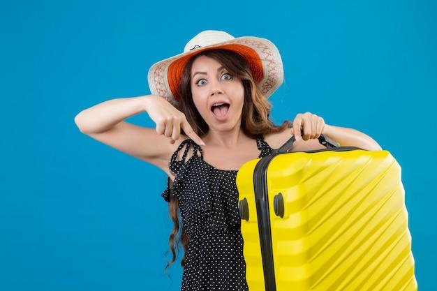 Giovane bella ragazza in abito a pois in cappello estivo che tiene la valigia che punta con il dito ad esso guardando la telecamera sorpreso in piedi su sfondo blu