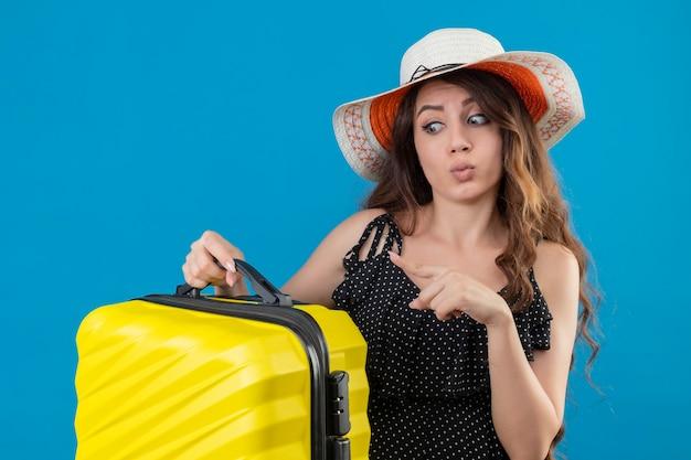 Giovane bella ragazza in abito a pois in cappello estivo che tiene la valigia che punta con il dito ad esso guardando sorpreso e confuso in piedi su sfondo blu
