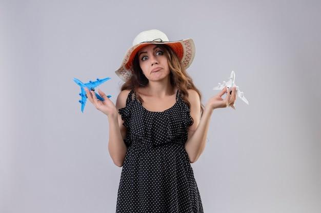 Giovane bella ragazza in vestito a pois in cappello estivo che tiene aeroplani giocattolo all'oscuro e confuso che guarda l'obbiettivo in piedi con le braccia alzate non avendo risposta su sfondo bianco