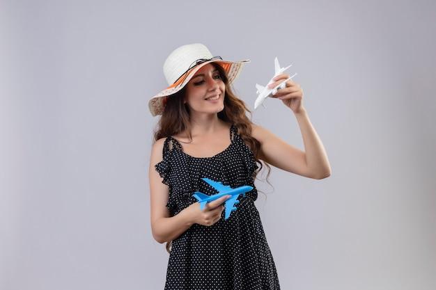 Giovane bella ragazza in abito a pois in cappello estivo che tiene aeroplani giocattolo cercando gioiosa sorridente felice e positivo in piedi su sfondo bianco