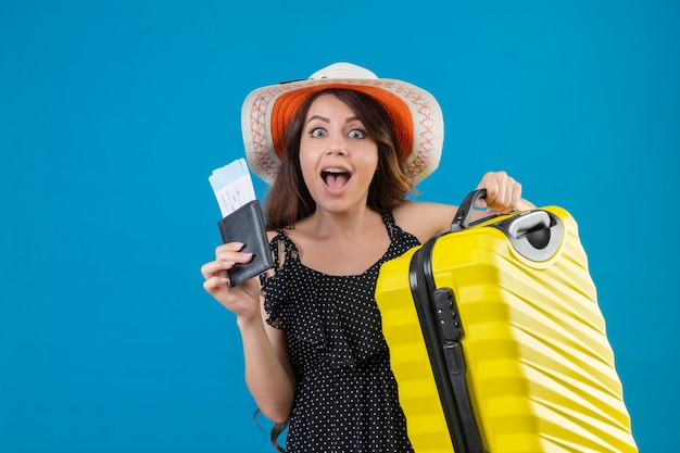 Young beautiful girl in dress in polka dot in summer hat standing with suitcase holding air tickets looking surprised and happy over blue background