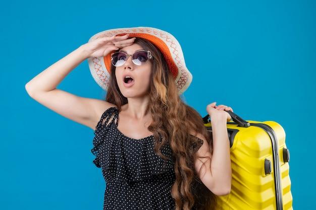 Giovane bella ragazza in abito a pois in cappello estivo indossando occhiali da sole tenendo la valigia alzando lo sguardo sorpreso e scioccato in piedi su sfondo blu