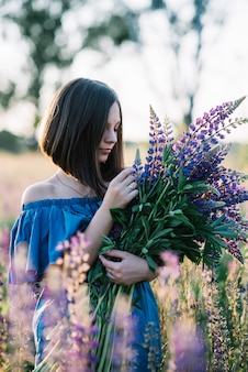 Young beautiful girl in a dress stands in a field of lupins. girl holds a large bouquet of purple lupins in a flowering field. blooming lupine flowers. environmentally friendly. nature concept