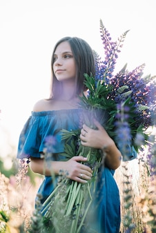 Young beautiful girl in a dress stands in a field of lupins. girl holds a large bouquet of purple lupins in a flowering field. blooming lupine flowers. environmentally friendly.