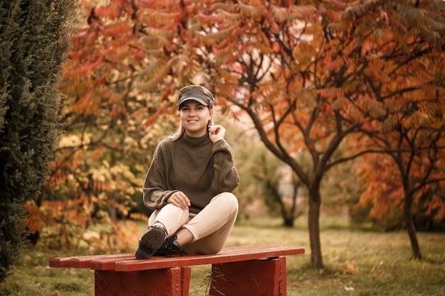 美しい木々のある秋の公園で、スタイリッシュな服、緑のセーター、ベージュのパンツを着た美しい少女