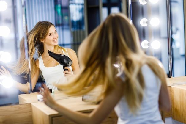 아름 다운 소녀는 거울 앞에서 긴 헤어 드라이어를 말립니다.