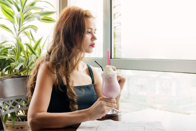 Молодая красивая девушка пьет молочный коктейль со вкусом клубники в ресторане на фоне окна при дневном свете. девушка держит стакан безалкогольного коктейля.