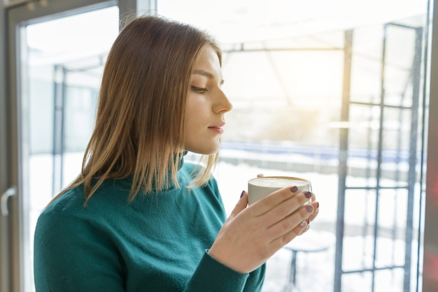Young beautiful girl drinking coffee, standing in profile, looking out the window