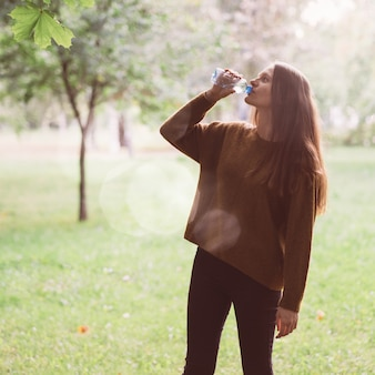 Young beautiful girl drinking water from a plastic bottle on street in park in autumn or winter.