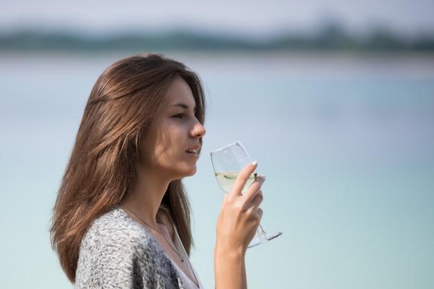 아름 다운 소녀는 유리에서 와인을 마신다.